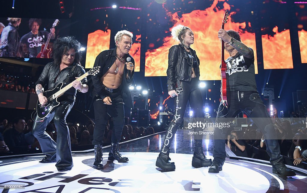 Recording artists Steve Stevens, Billy Idol, Miley Cyrus, and Billy Morrison perform onstage at the 2016 iHeartRadio Music Festival at T-Mobile Arena on September 23, 2016 in Las Vegas, Nevada.