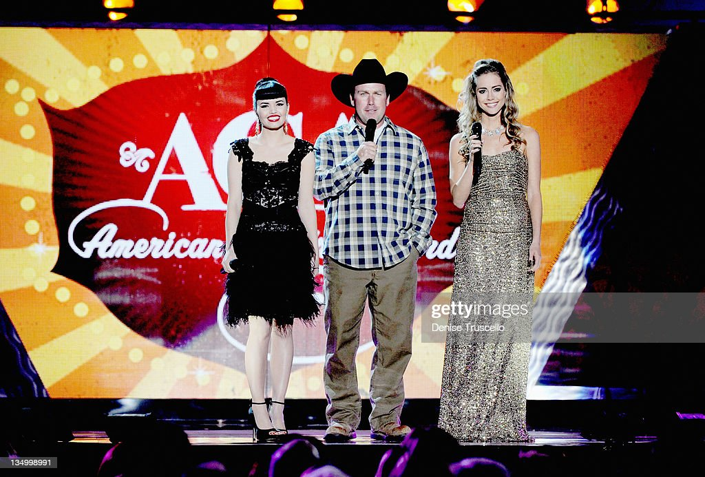 Recording artists Susie Brown and Danelle Leverett of The JaneDear Girls and comedian/singer Rodney Carrington (C) speak onstage during the 2011 American Country Awards at MGM Grand Garden Arena on December 5, 2011 in Las Vegas, Nevada.