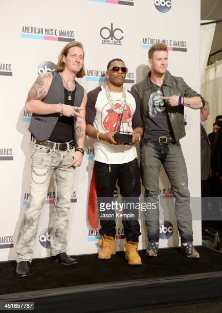 Recording artists Tyler Hubbard and Brian Kelley of Florida Georgia Line and Nelly pose in the press room during the 2013 American Music Awards at...