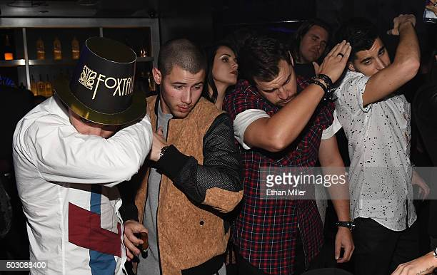 Recording artists/actors Joe Jonas and Nick Jonas and friends pose at Foxtail Nightclub at SLS Las Vegas during a New Year's Eve celebration on...