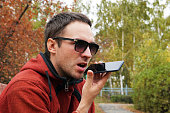 Recording on dictaphone. leisure, technology, communication and people concept - hipster man using voice command recorder or calling on smartphone at autumn park. dictate the thoughts in entry.