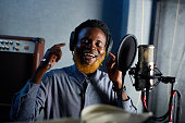 Happy African man singing and recording his songs in studio