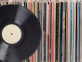 Vinyl records in a row. One record is standing in front. On the record label there is some copy space.