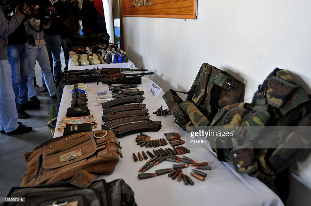 Recovered weapons and ammunition, which police say were seized following the arrests of suspects linked to an attack against five paramilitary policemen last week, are displayed to journalists during a press conference in Srinagar on March 19, 2013. Police in Indian-administered Kashmir on March 19 said they had arrested four people including a Pakistani national from the Lashkar-e-Toiba militant group over an attack that left five policemen dead. Two heavily armed militants attacked a group of Central Reserve Police Force personnel in a compound of a police public school last week, killing five of them and injuring ten others including four civilians.