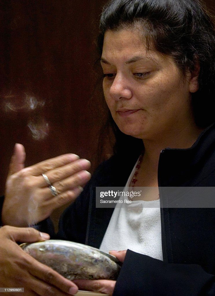 Recovering drug addict, Peanuts Tuttle, cleanses herself with the smoke of white sage burning in an abalone shell, a symbol of Mother Earth's womb, during a White Bison talking group meeting, February 6, 2007, at the Native American Health Center in Sacramento, California. This ritual is called 'smudging.'