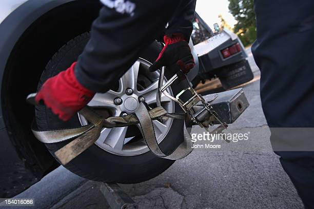 Recovery agent or 'repo man' Jeff Grevelding secures a car for towing while repossessing cars on October 11 2012 in Syracuse New York Grevelding who...