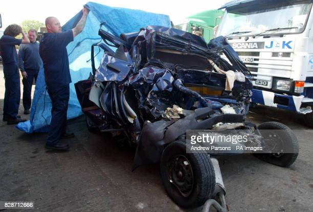 Recovery workers cover up the Ford Escort which was involved in the crash on the M1 where a family of four including two young children were killed...