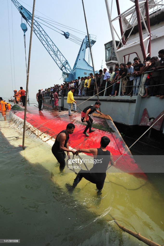 Recovery workers prepare to raise a sunken ferry in Munshigong on March 14, 2012. Rescue workers and divers in Bangladesh on March 14 pulled scores of bodies from the wreckage of a ferry that sank after being hit by an oil barge, as the death toll rose to 112. The packed Shariatpur 1 vessel, carrying about 200 passengers, capsized in the early hours of Tuesday morning after a collision with the barge in the Meghna river, 40 kilometres (25 miles) southeast of the capital Dhaka.