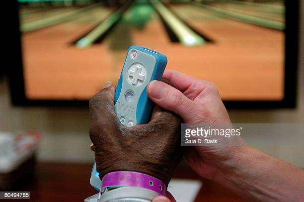 Recreation therapist Elizabeth Penny holds James Mann's hand while he uses the control of Nintendo's Wii gaming system to play a bowling game during...