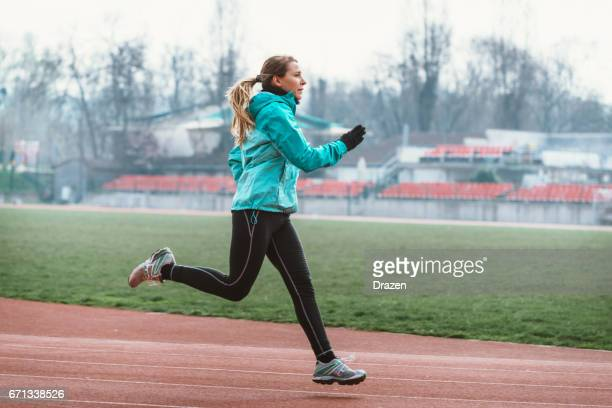 Recreational female athlete stretching, jogging and doing exercises outdoors