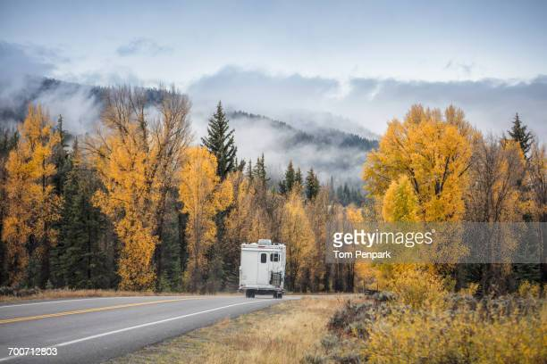 Recreational vehicle driving on road in autumn