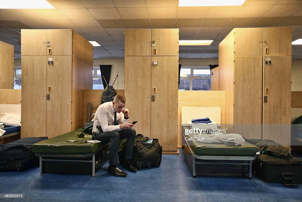 A recruit checks his phone in his dormitory after arriving at Commando Training Centre Royal Marines on December 01, 2014 in Lympstone, United Kingdom. Recruit training lasts for 32 weeks for Marines and 64 weeks for officers and is one of the longest and most physically demanding specialist infantry training regimes in the world. On the 28th October 2014, the Royal Marines celebrated their 350th birthday year. Since then, Marines have taken part in more battles on land and sea around the world than any other branch of the British Armed Forces.
