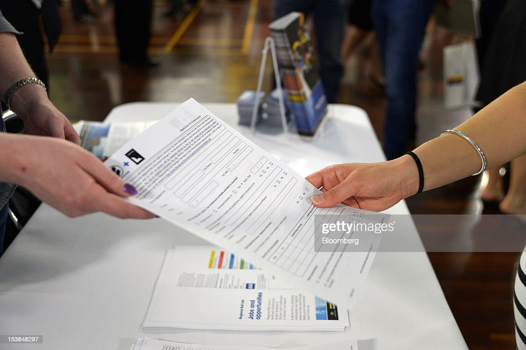 A recruiter hands out an application form to a job seeker at a jobs and skills expo run by the Australian government in Melbourne, Australia, on Thursday, Oct. 4, 2012. Australia's unemployment rate probably climbed to 5.3 percent last month from 5.1 percent in August, according to the median estimate of economists surveyed by Bloomberg News. Photographer: Carla Gottgens/Bloomberg via Getty Images