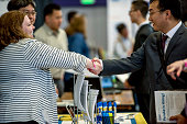 A recruiter left shakes hands with a job seeker during a career fair at San Francisco State University in San Francisco California US on Friday April...