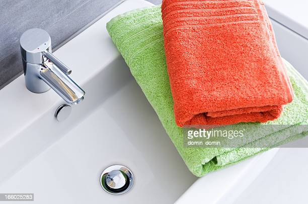 Rectangular bathroom sink with one green and one orange towel