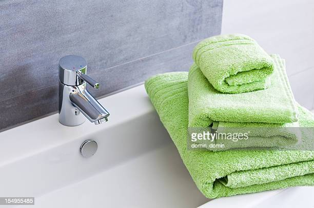 Rectangular bathroom sink with tap and three green towels