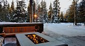 Modern, cozy fire pit with wooden benches nearby and within a snow filled scene at sunrise/sunset...sun is peeking through a row of evergreen trees in the distance.
