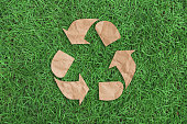 recycle symbol on green grass background top view. eco and save the earth concept.