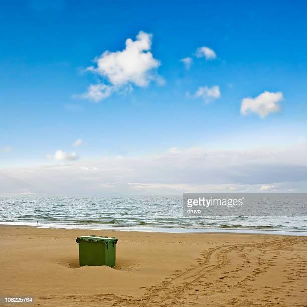 Papelera de reciclaje en la playa con el cielo azul de fondo