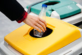Woman hand throwing a plastic bottle into a yellow recycling container in the street