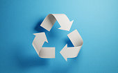 Recycling symbol made of paper on blue background. Horizontal composition with copy space. Green energy concept.