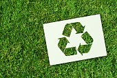 Ecology concept: recycling. Green recycling symbol obtained on perforated white sheet of paper, inside a green grass meadow. XXXL size image.
