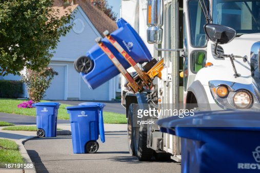 Recycling Truck Lifting Up Container Along Neighborhood Curb