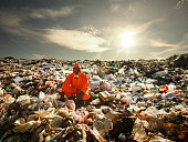 Portrait of recycling worker among garbage bags on the landfill