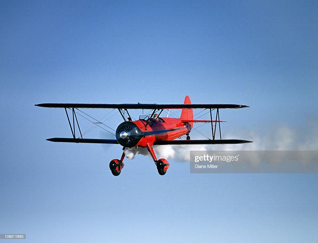 Red 1943 Stearman bi-plane in flight with tail smoke, St. Francis, Kansas, USA