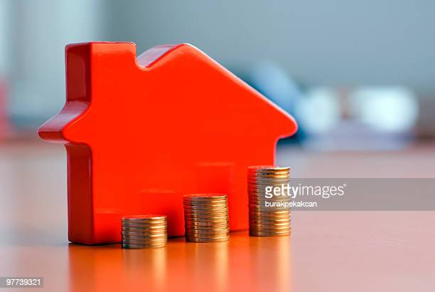 Red 3D house model next to growing stacks of coins