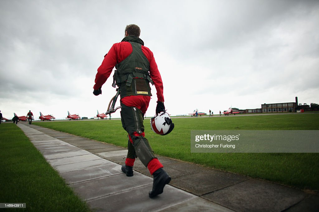 Red 4, Flight Lieutenant James McMillan walks to his aircraft for a practice flight with the Red Arrows at RAF Scampton on June 22, 2012 in Scampton, England. The famous Royal Air Force Red Arrows are perfecting their routine for a fly past next week when the Olympic torch arrives in Norfolk and also for an audience of millions during the opening ceremony of the London 2012 Olympics.