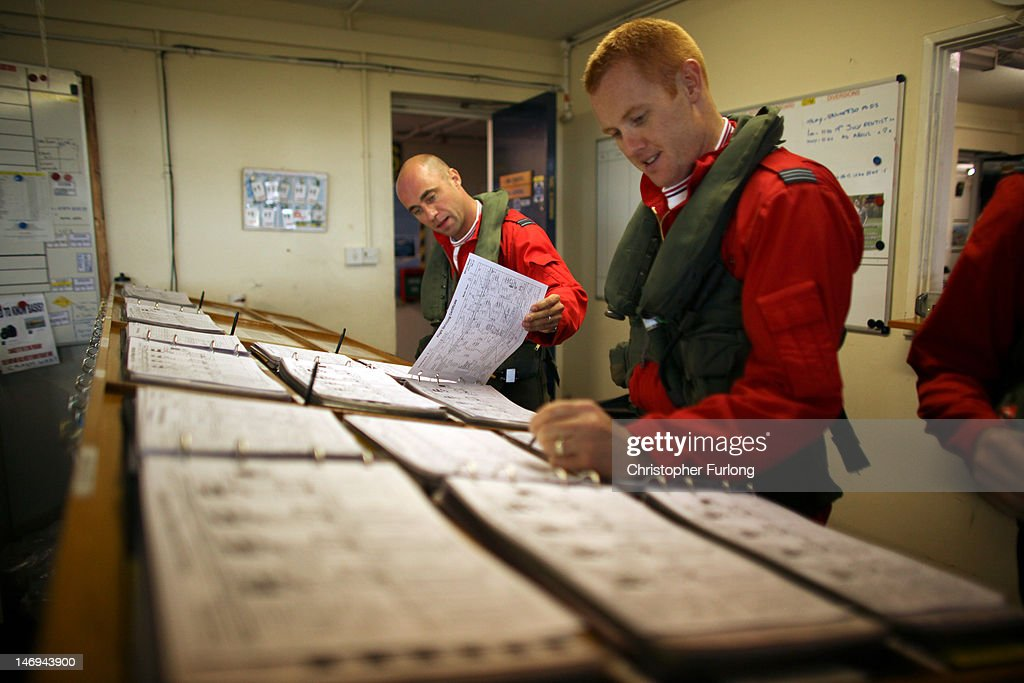 Red 6, Flight Lieutenant Ben Plank (L) and Red 2, Flight Lieutenant Martin Pert, sign for their Hawk jets as they prepare to leave for a display at RAF Scampton on June 22, 2012 in Scampton, England. The famous Royal Air Force Red Arrows are perfecting their routine for a fly past next week when the Olympic torch arrives in Norfolk and also for an audience of millions during the opening ceremony of the London 2012 Olympics.