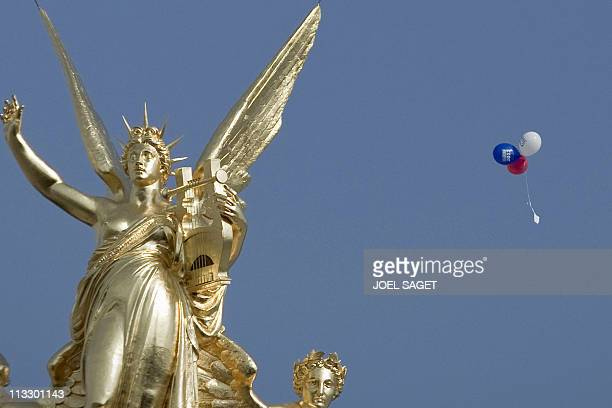A red a white and a blue ballon the colors of the French flag fly over Paris next to the statue of Joan of Arc before the speech of the president of...