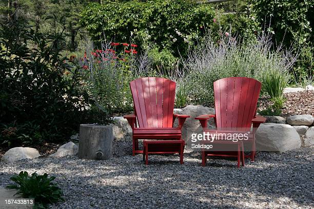 Red Adirondack Chairs And Blue Russian Sage In The Garden