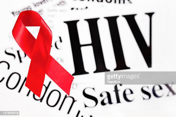 Red AIDS awareness ribbon on HIV related headlines