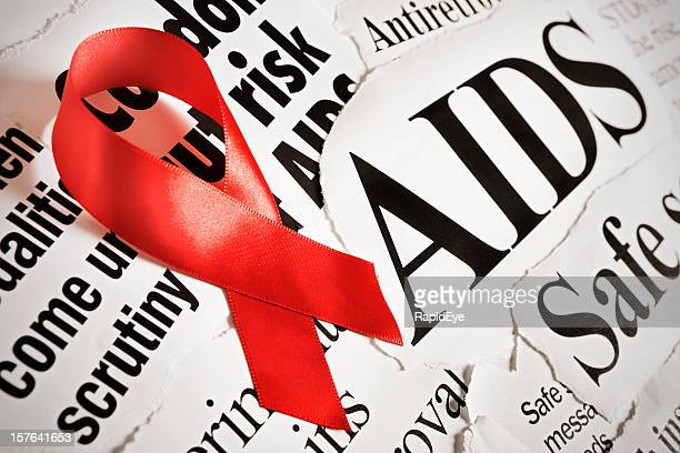 Red AIDS ribbon on headlines about aspects of the disease