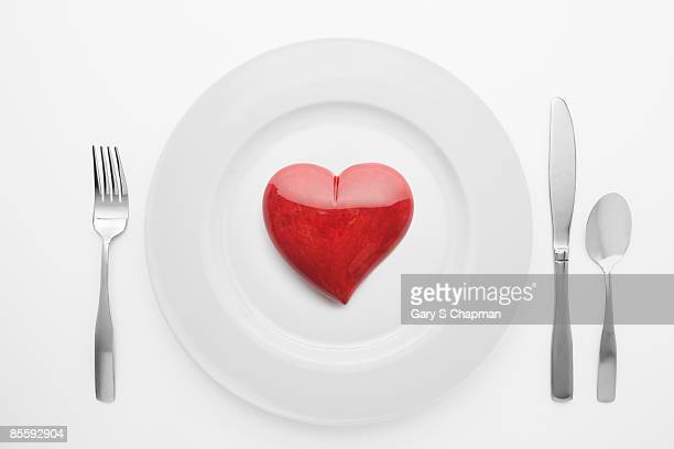 Red alabaster heart on white plate