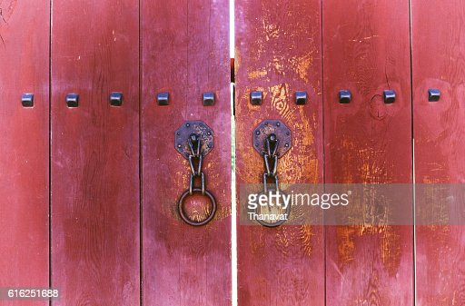 red ancient wooden gate with two door knocker : Foto de stock