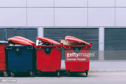 Red and blue garbage bins on roadside against wall