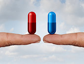 Red and blue pill choice as fingers holding medication capsules as a symbol of choosing between truth and illusion or knowledge or ignorance or pharmaceutical treatment option concept with a 3D render