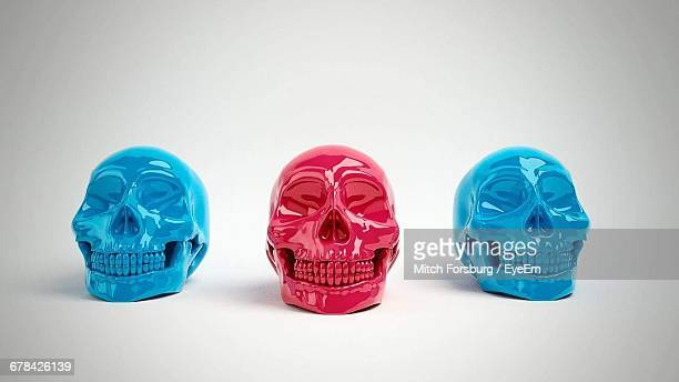 Red And Blue Skulls Decorations Against White Background