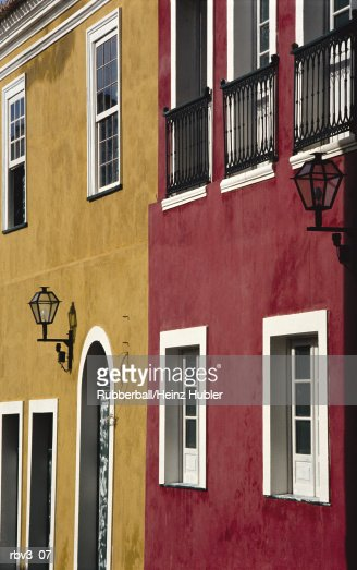 red and dark yellow stucco homes with white framing around windows and doorways in europe