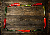 Red and green chili pepper on plate on wooden background.
