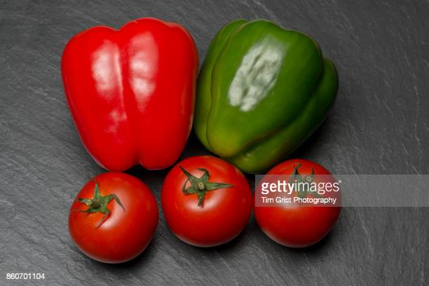 Red and Green Peppers and Tomatoes on Slate Surface