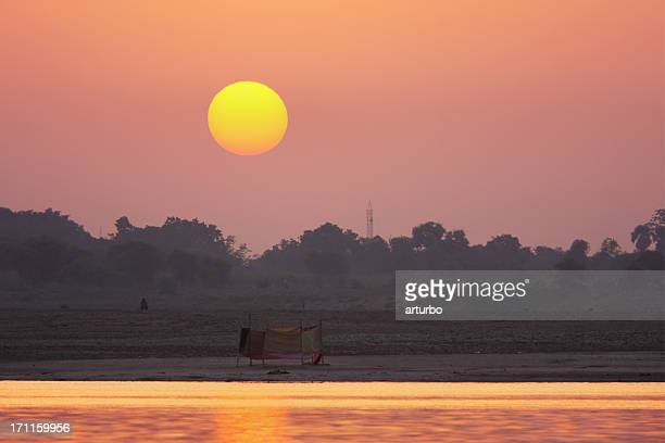 red and orange sunset over river in India