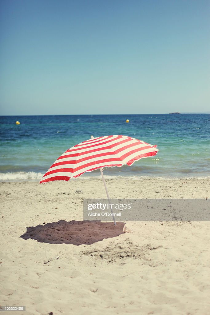 A Red And White Beach Umbrella On The Beach Stock Photo ...