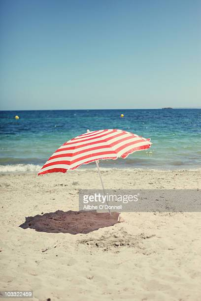 A red and white beach umbrella on the beach