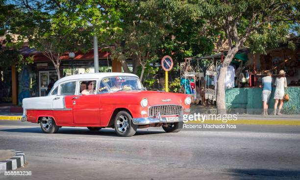 Red and white old Chevrolet car working as taxi and driving along the main Varadero avenue