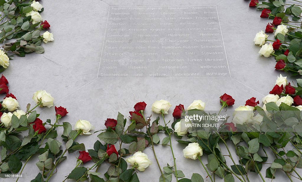 Red and white roses are laid down on a memorial plate at the former Nazi concentration camp in Buchenwald near Weimar, eastern Germany, on Holocaust Day, January 27, 2013. A ceremony took place to commemorate the victims of the Holocaust.