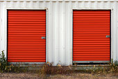 An image of a white storage unit with bright red doors.